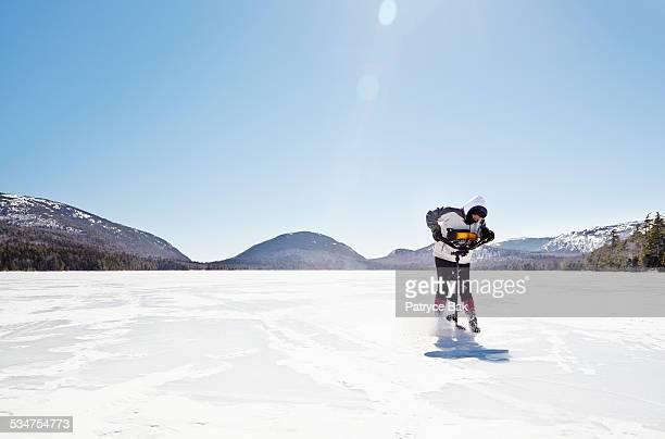WOMAN ICE FISHING DRILLS ON FROZEN LAKE IN ACADIA