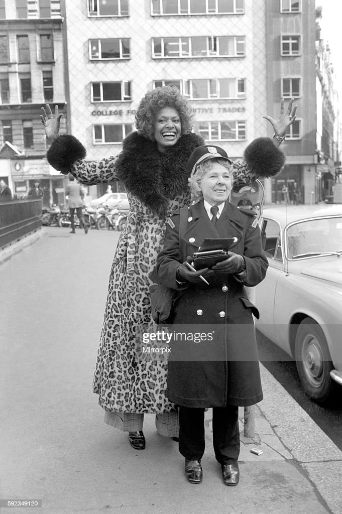 Model Lorne Lesley wearing a long leopard skin coat with fur collar standing behind a traffic warden February 1975 : News Photo