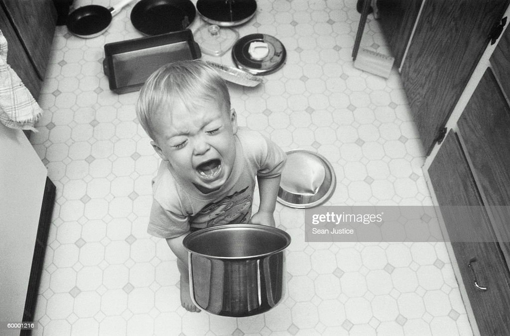 BOY PLAYING WITH POTS AND PANS, SCREAMING : Stock Photo