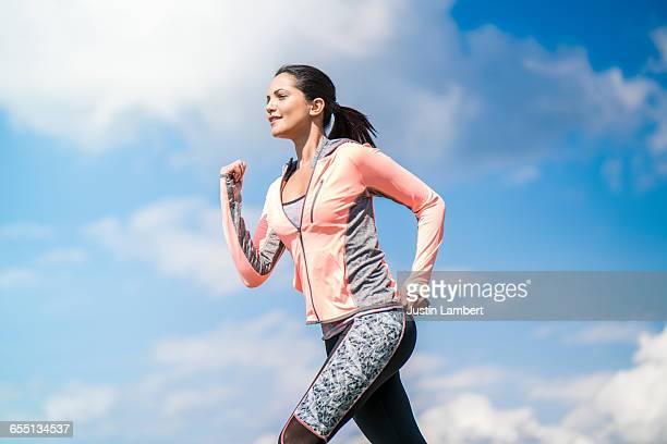 woman running against vivid sky - langärmlig stock-fotos und bilder