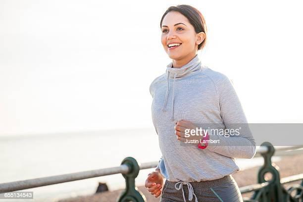 WOMAN RUNNING ALONG BEACH PROMENADE