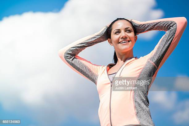 woman stretching while on a run - long sleeved stock photos and pictures