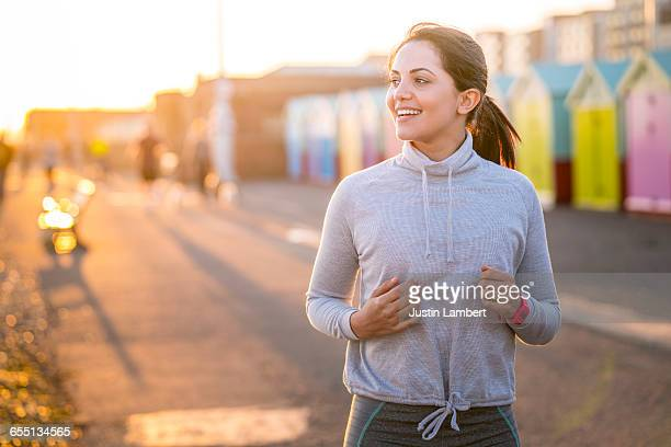 woman running along beachfront - long sleeved stock photos and pictures