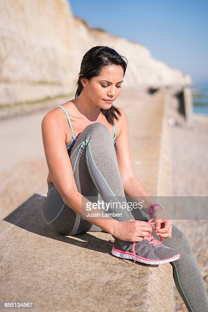 WOMAN TIES SHOELACES WHILE ON A RUN