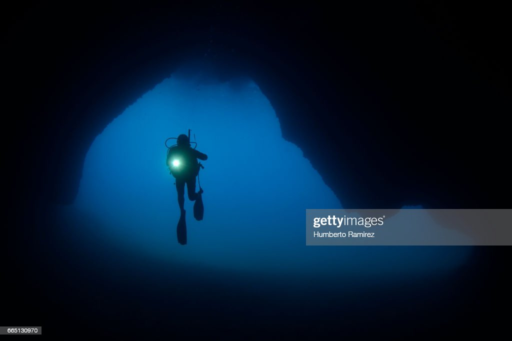 DIVER EXPLORING AN UNDERSEA CAVE. : Stock Photo