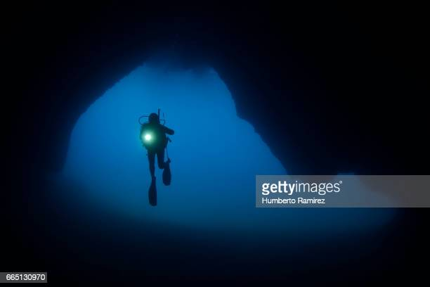 diver exploring an undersea cave. - speleology stock pictures, royalty-free photos & images