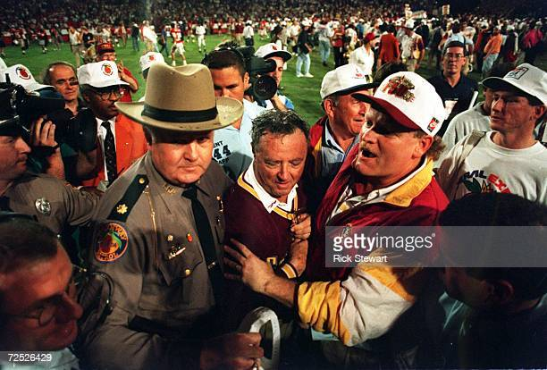 FLORIDA STATE SEMINOLES HEAD COACH COACH BOBBY BOWDEN IS ESCORTED OFF THE FIELD AFTER HIS TEAM DEFEATED NEBRASKA 1816 IN THE 1994 ORANGE BOWL IN...