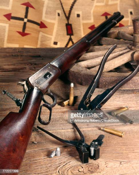 STILL LIFE OF MODEL 1886 WINCHESTER .40 82 CALIBER LEVER ACTION RIFLE AND PERIOD CARTRIDGE LOADING TOOLS