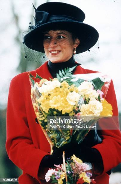 PRINCESS DIANA AT SANDRINGHAM ON CHRISTMAS DAY, THE PRINCESS IS WEARING A RED COAT AND A BROAD-BRIMMED BLACK HAT, SHE IS CARRYING A BOUQUET OF FLOWERS