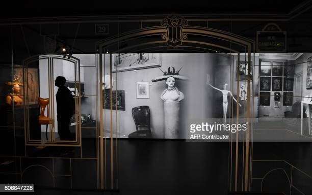 A visitor views items during the Dior exhibition that celebrates the seventieth anniversary of the Christian Dior fashion house on July 3 2017 in...