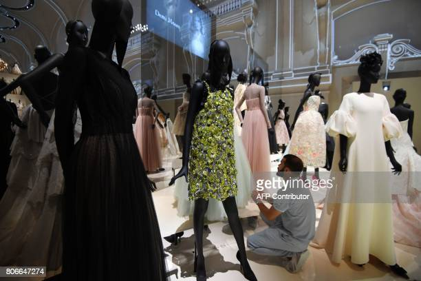 A man adjusts dresses prior to the opening of the Dior exhibition that celebrates the seventieth anniversary of the Christian Dior fashion house on...