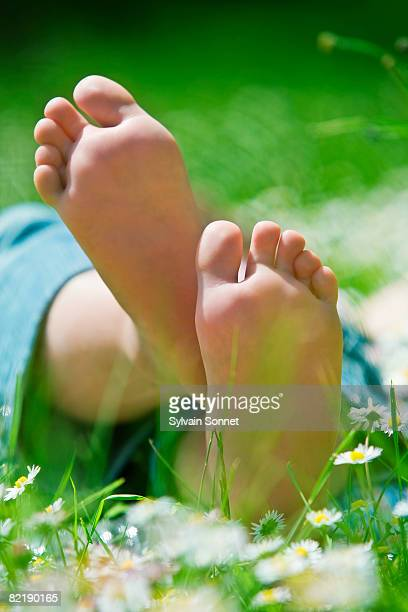 GIRL LYING ON GRASS, CLOSE UP OF FEET