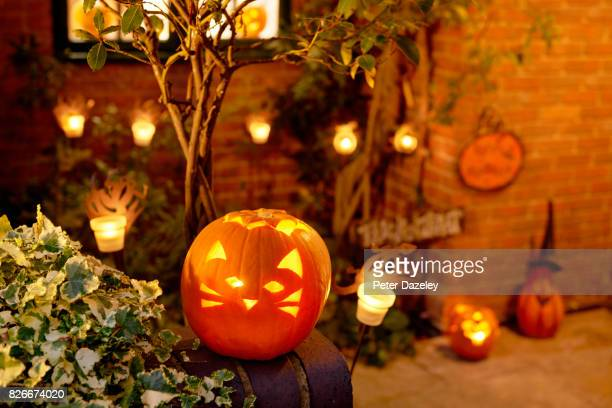halloween, lit pumpkin outside residential house - halloween stock pictures, royalty-free photos & images