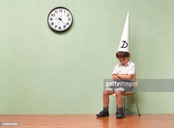 humiliated schoolboy with dunces hat in classroom - penalty stock pictures, royalty-free photos & images