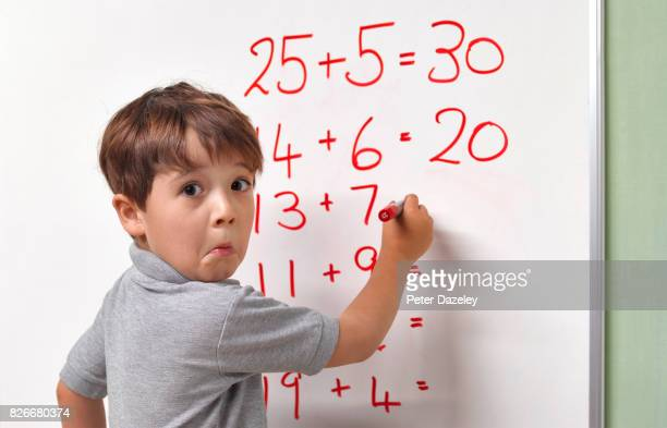 pupil baffled by maths sum on classroom whiteboard - wiskunde stockfoto's en -beelden