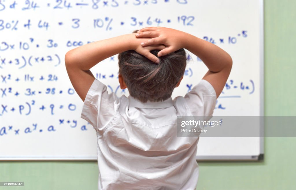 JUNIOR PUPIL AMAZED BY MATHS ON CLASSROOM WHITEBOARD : ストックフォト