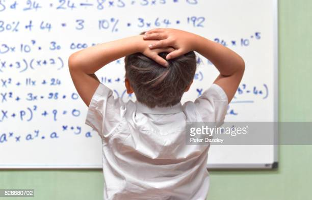 JUNIOR PUPIL AMAZED BY MATHS ON CLASSROOM WHITEBOARD