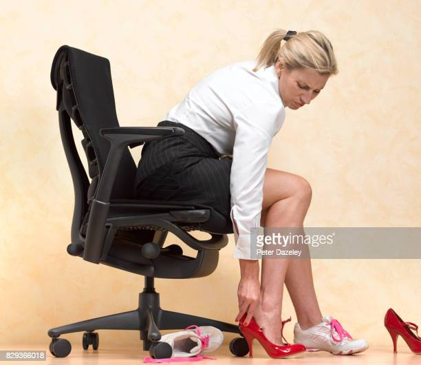 BUSINESSWOMAN CHANGING IN TO UNCOMFORTABLE HEELS TO LOOK SMART IN THE OFFICE