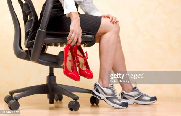 having to wear uncomfortable high heels at work - legs and short skirt sitting down stock pictures, royalty-free photos & images