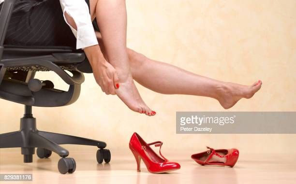removing painful killer heels to massage feet in office - hallux valgus photos et images de collection