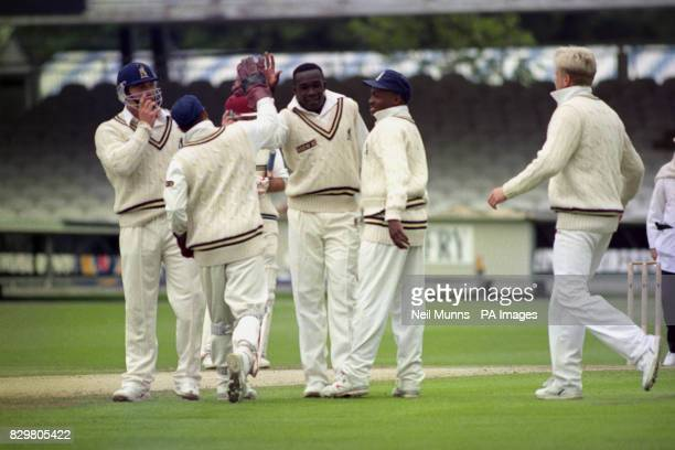 IS CONGRATULATED BY WARWICKSHIRE WICKETKEEPER KEITH PIPER AND BRIAN LARA AFTER CAPTURING THE WICKET OF MIDDLESEX BATSMAN KEITH BROWN IN THE BRITANNIC...