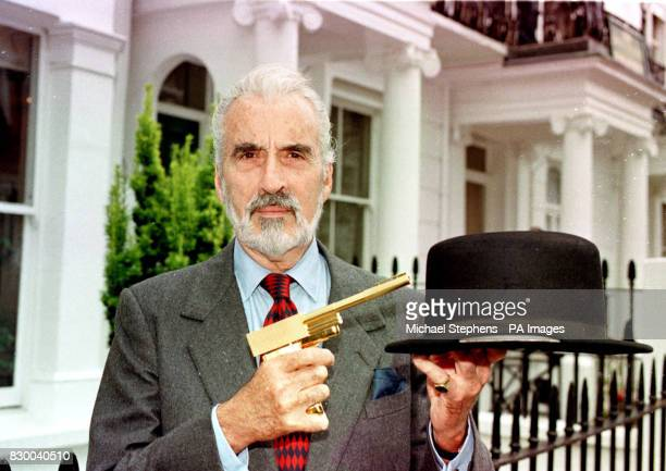 IN 'THE MAN WITH THE GOLDEN GUN' HOLDS A GOLDEN GUN THE METAL BOWLER HAT USED BY ODDJOB TO PROMOTE THE FORTHCOMING BOND AUCTION AT CHRISTIE'S