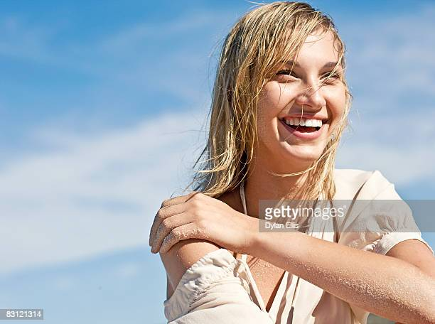 young woman with wet hair smiling at the beach. - wet hair stock pictures, royalty-free photos & images
