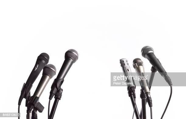 press conference microphones with white copy space - press conference stock pictures, royalty-free photos & images