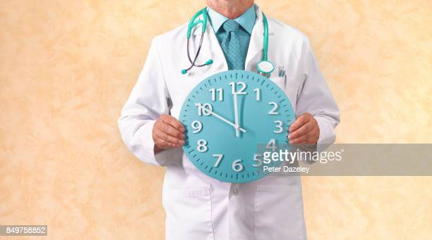OVERWORKED NHS GP HOLDING CLOCK