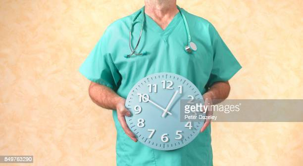 OVERWORKED NHS DOCTOR HOLDING CLOCK