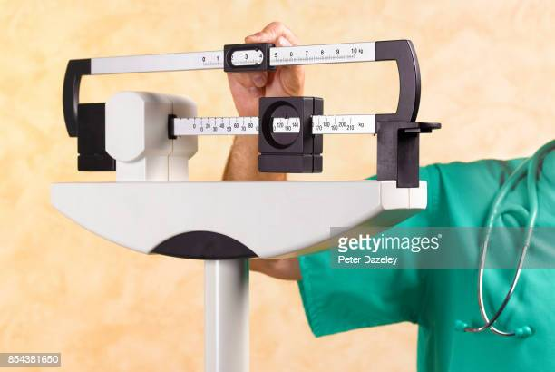 dr with overweight patient on medical scales - scale stock pictures, royalty-free photos & images