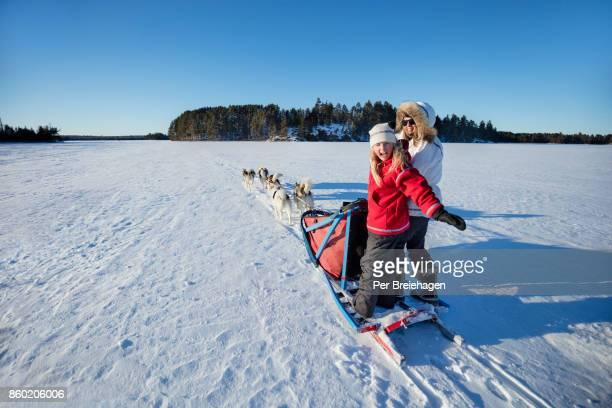 MOTHER AND DAUGHTER DOG SLEDDING ON MINNESOTA LAKE