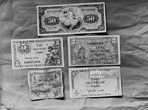 Newlyissued Deutsche Mark notes which are replacing the old Reichsmark and Rentenmark in West Germany June 1948 The note at bottom left is obsolete...