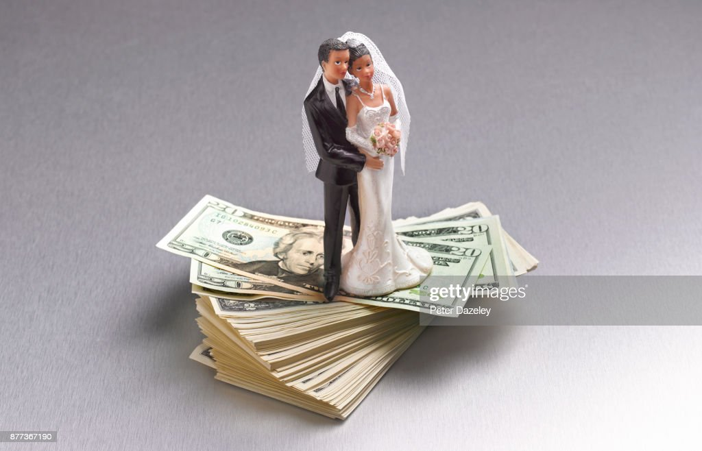 COUPLE STANDING ON US DOLLARS : Stock Photo