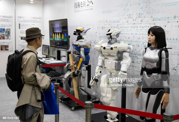 A man looks at the HRP4C humanoid robot in the National Institute of Advanced Industrial Science and Technology booth during the International Robot...