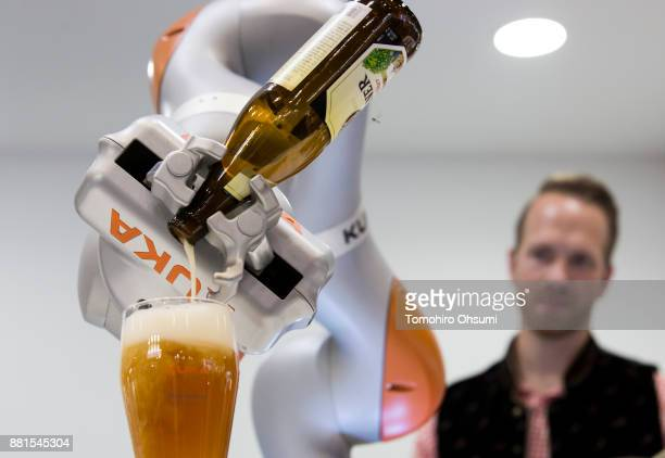 Kuka AG robotic arm pours a bottle of beer into a glass during a demonstration at the International Robot Exhibition 2017 at the Tokyo Big Sight on...