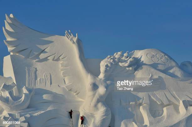 Workers carve the main sculpture 'Snow Song Winter Olympics' for the 30th Harbin Sun Island international Snow Sculpture Art Exposition on December...