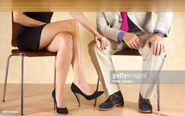 GIRL WITH HER HAND ON A MAN'S KNEE UNDER THE TABLE