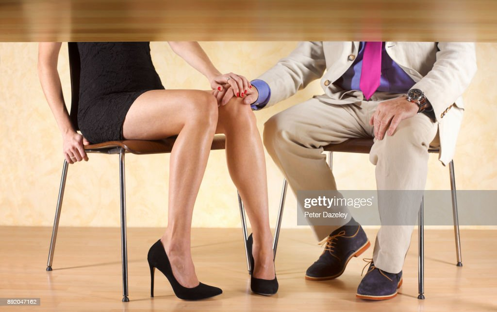 COUPLE HOLDING HANDS UNDER THE TABLE : Stock Photo
