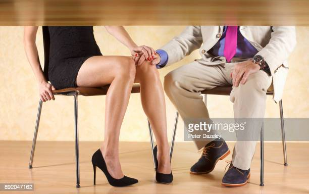 COUPLE HOLDING HANDS UNDER THE TABLE