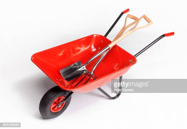 wheelbarrow with fork and spade on white background - gardening equipment stock pictures, royalty-free photos & images