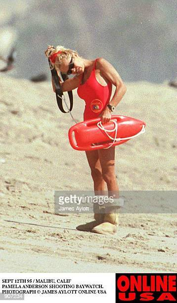 SEPT 12TH 95 HOLLYWOOD CALIF PAMELA ANDERSON SHOOTING BAYWATCH SHE WEARS HER WINTER UGH BOOTS ON THE HOT BEACH