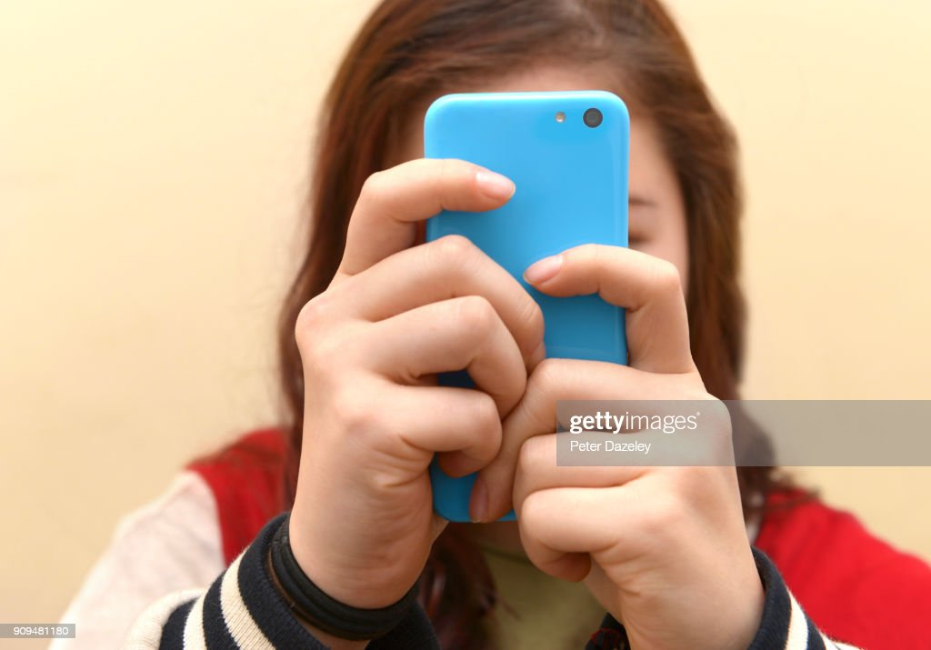 OBSESSIVE TEENAGER TEXTING ON SMART PHONE : Stock Photo