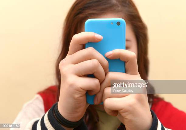 obsessive teenager texting on smart phone - text stock pictures, royalty-free photos & images