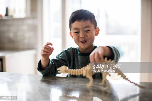 young boy playing with dinosaur model at home - dinosaure photos et images de collection