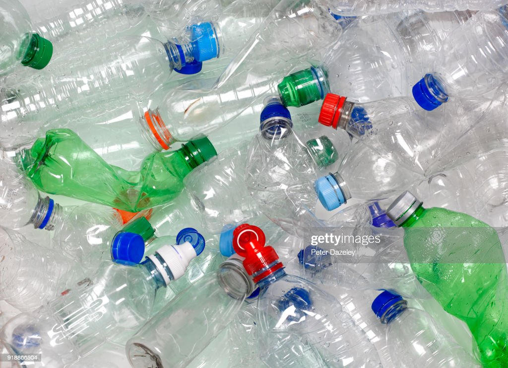 WATER BOTTLES IN RECYCLING BIN WITH RECYCLABLE CAPS : Foto stock