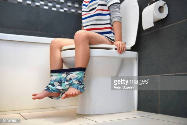 YOUNG BOY SITTING ON TOILET