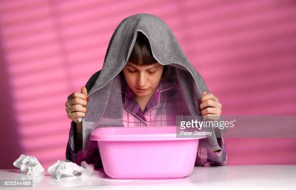woman with cold/flu inhaling steam from a bowl - cold and flu stock pictures, royalty-free photos & images