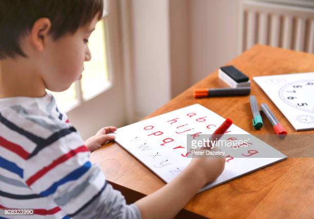 boy practicing writing the alphabet - ホームスクーリング ストックフォトと画像