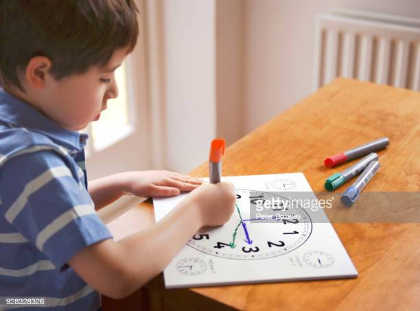 boy learning to tell the time - clocks go forward stock pictures, royalty-free photos & images